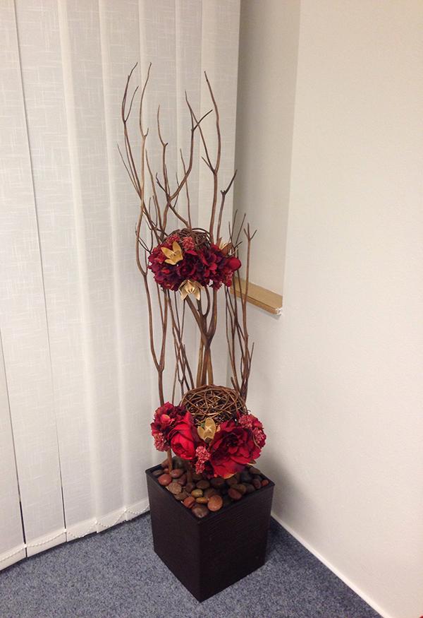 Vysoká dekorace do zasedací místnosti z proutí, umělých a sušených květin a hnědé nádobě. Floristika Klára Uhlířová.