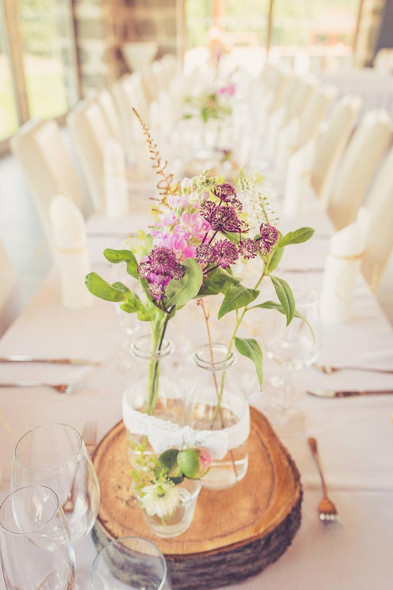 Květinová dekorace ve váze ozdobené krajkou, to vše na dřevěném špalíku. Floristika Klára Uhlířová Brno