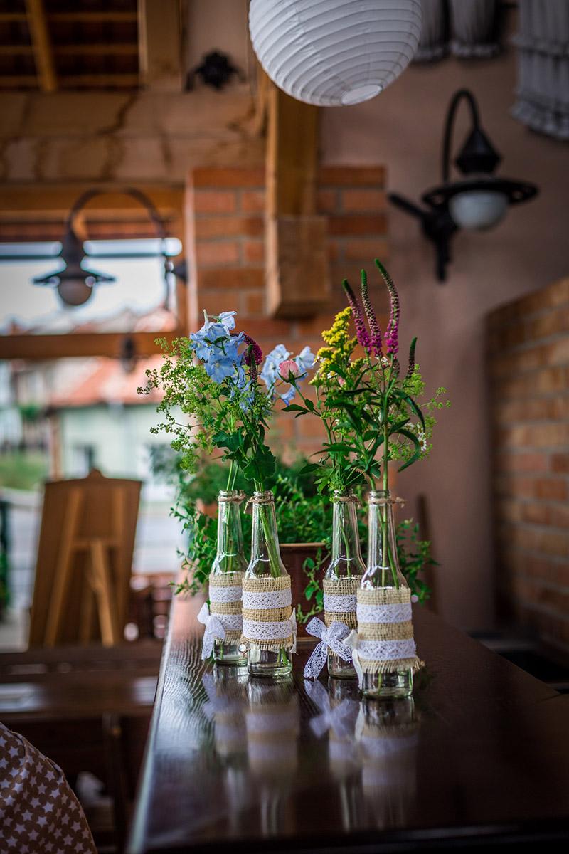 Květinové dekorace na stoly. Vázičky ozdobené jutou a krajkou s lučními květinami. Svatební floristika Klára Uhlířová Brno