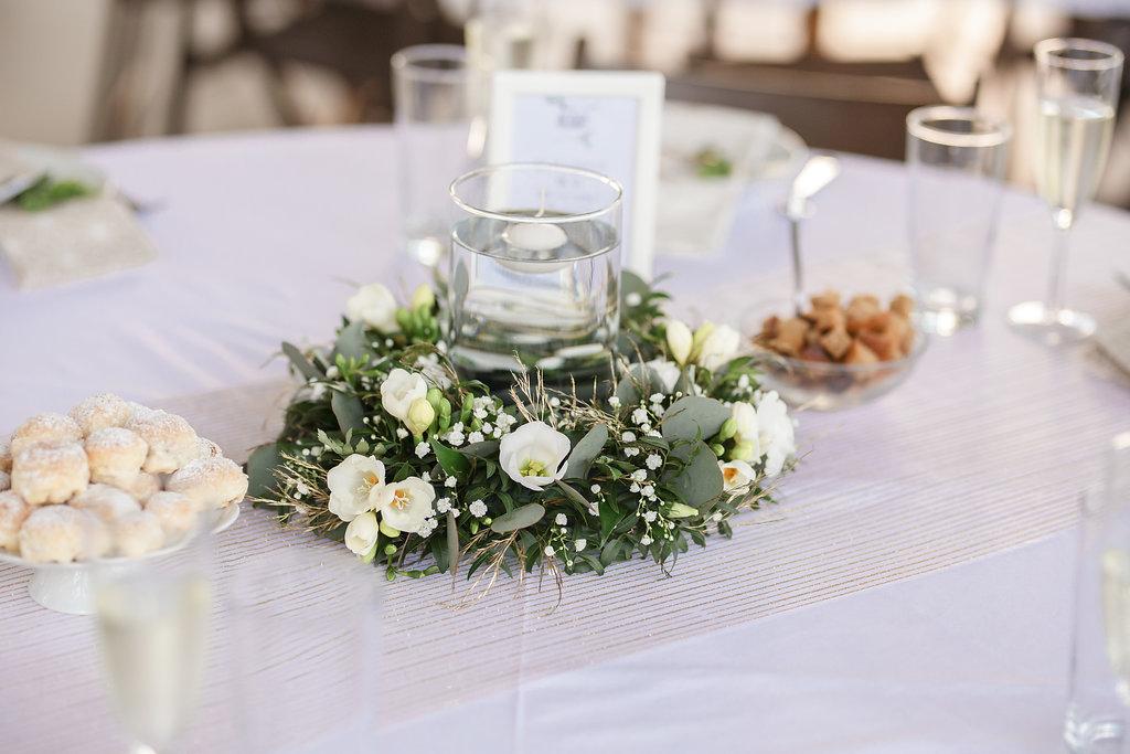 Dekorace na kulaté stoly. Vypichovaný věnec v bílo - zlato - zelené barvě se svíčkou uprostřed. Svatební květiny Klára Uhlířová Brno