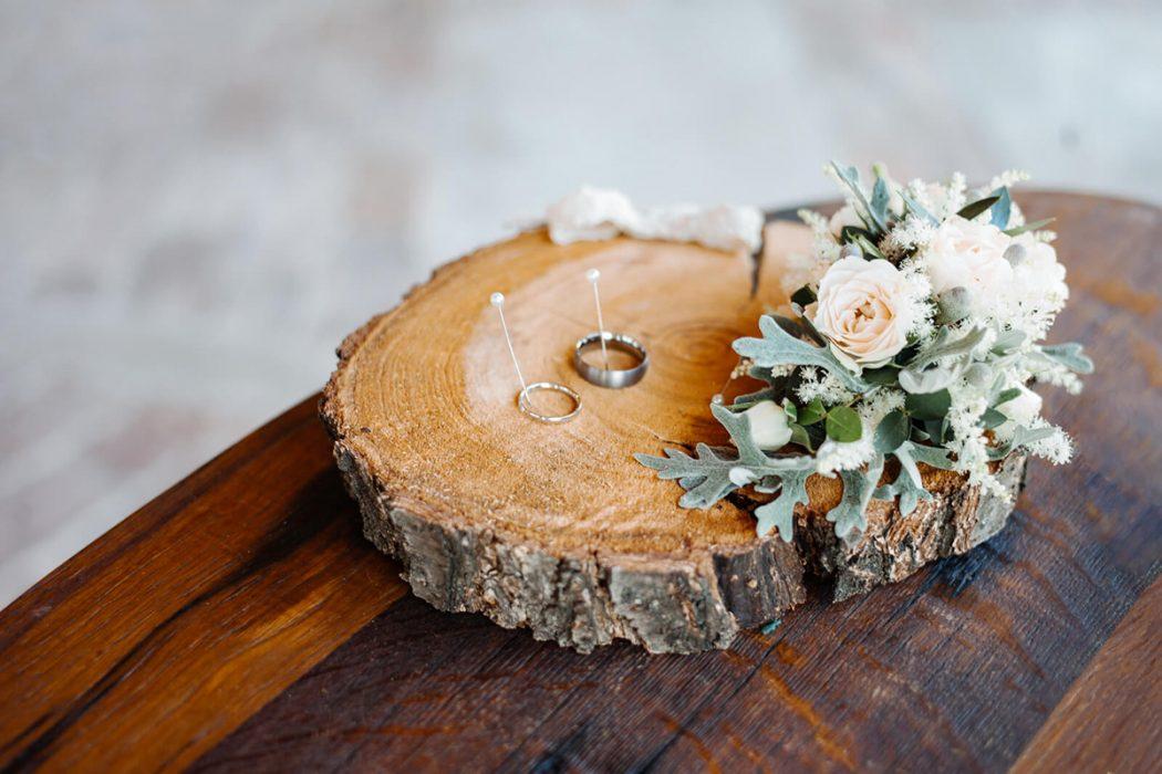 Dřevěné polínko jako podnos na prstýnky. Polínko je dozdobené květinovou dekorací v krémové a stříbrné barvě. Svatební květiny Klára Uhlířová.