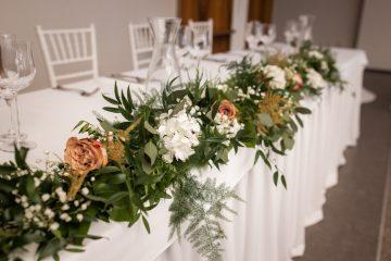 Bohatá girlanda na stůl novomanželů. Hortenzie, růže, nevěstina závoj a zeleň. Svatební květiny Klára Uhlířová Brno