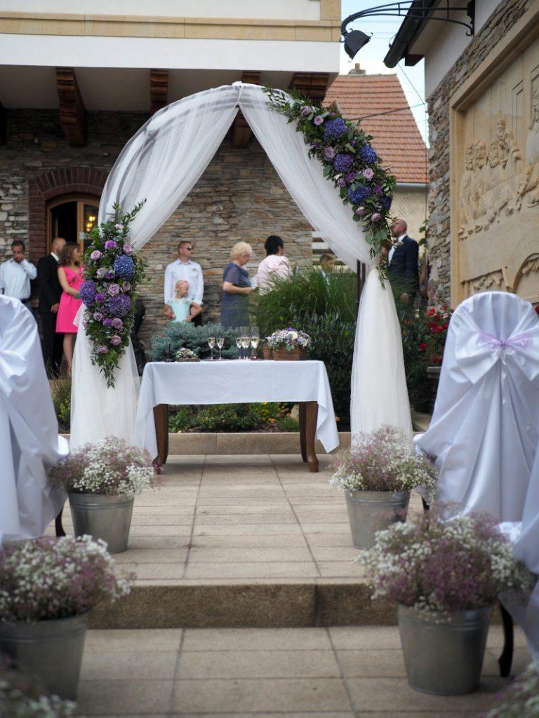 elegantní oblouková slavobrána dozdobená voály a květinami.