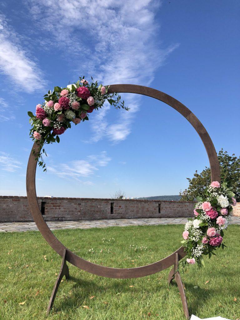 Kruhová slavobrána s růžemi, karafiáty a nevěstiným závojem. Svatební květiny Klára Uhlířová